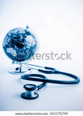 Global healthcare. Globe and stethoscope, studio shot.blue toned images. - stock photo