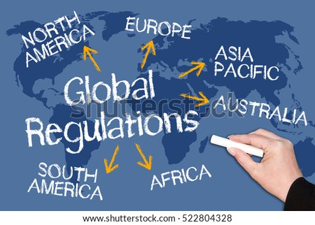 Global Regulations - blue chalkboard with world map and female hand with chalk