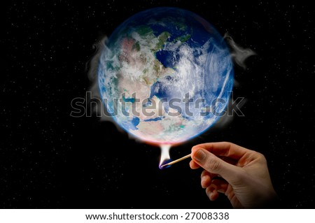 Global Warming a hand holding a match warming the globe - stock photo