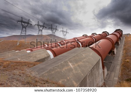 Global warming and renewable energy concept, penstock water pipes in a hydroelectric power plant on barren hillside with electric trabsmission line pylons against dramatic stormy sky - stock photo