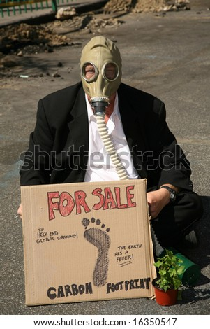 Global Warming concepts. a Business Man wears a Gas Mask and offers to sell his Carbon Footprint to help end Global Warming