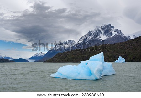 Global warming. Shatter of blue iceberg melts in front of The Gray Glacier, Patagonia, Chile - stock photo
