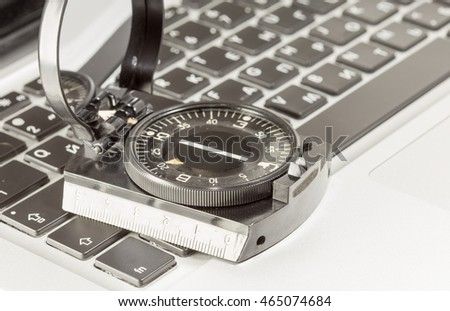 Global Web, wireless of GPS-navigation internet technology and success in business concept: Magnetic compass on a laptop or notebook PC keyboard