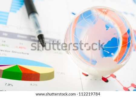 Global year report with glass globe and pen - stock photo
