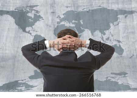 Globalization. Young business man with world map - stock photo