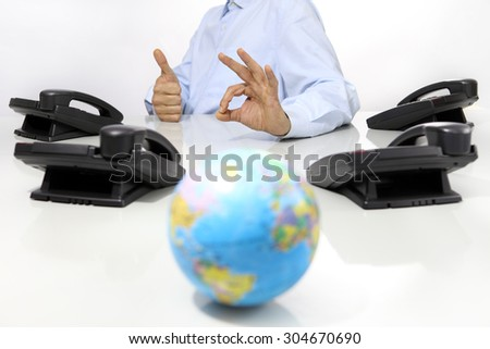 globe and like hand with office phones on desk, global international support concept - stock photo