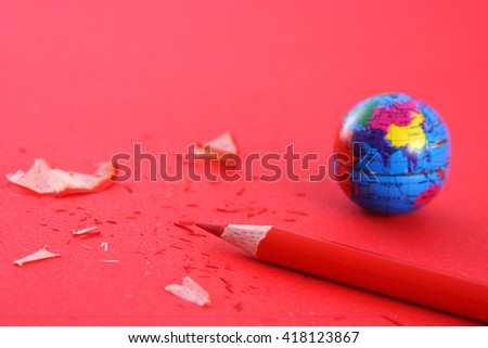 Globe and pencil on red background