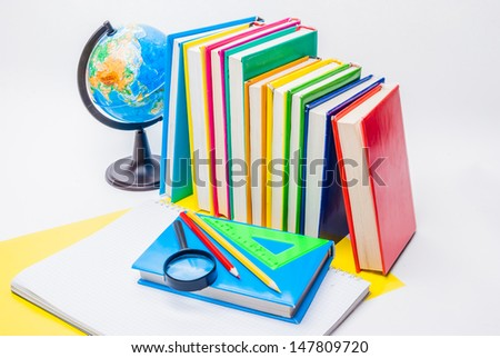 globe, colorful books, magnifier, pencils, ruler and notebook isolated on white - stock photo