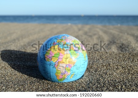 Globe Earth on the Beach near Ocean - stock photo