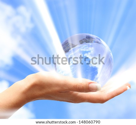 Globe in human hand against blue sky. - stock photo