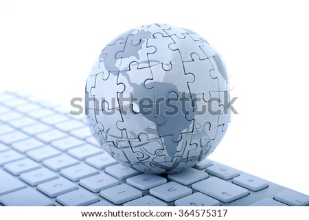 Globe jigsaw puzzle on a computer keyboard. Isolated on white background.