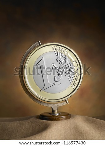 globe, map of the earth with euro coin on warm backdrop - stock photo