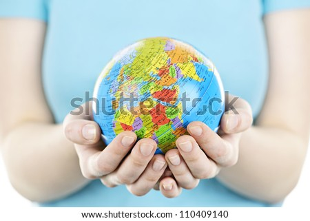 Globe of the planet Earth held in young female hands - stock photo