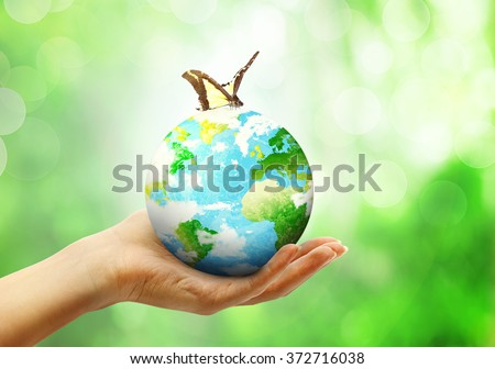 Globe on female human hand with butterfly in blur nature bokeh background with spfing leaves. Environment eco concept - stock photo
