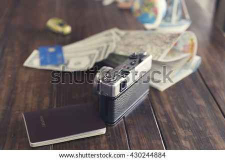 globe,  passport, credit card, banknote, camera,map, car and ship figurine on wooden table for use as traveling concept (vintage tone and selected focus)
