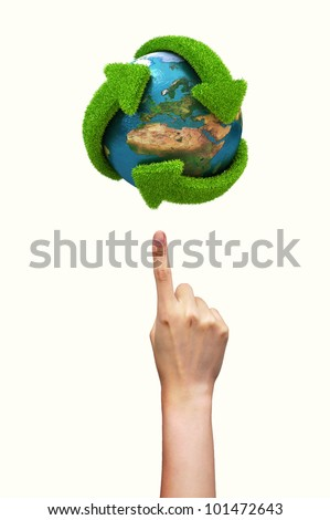 Globe with green arrows covered with grass presented on female finger. Elements of this image furnished by NASA
