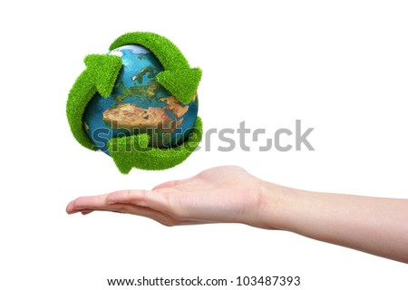 Globe with green arrows covered with grass presented on female hand. Elements of this image furnished by NASA