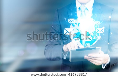 Globe with networking system, email icons and businessman using tablet. Elements of this image furnished by NASA