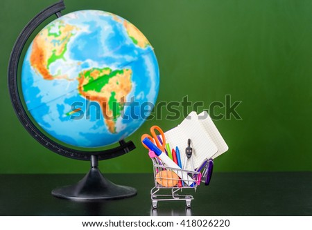 Globe with small shopping trolley with stationery near empty green chalkboard. Space for text - stock photo