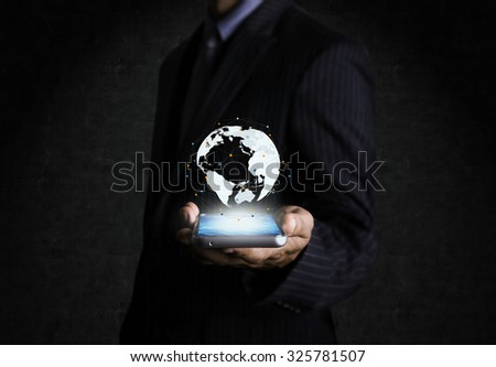 Globes on touch screen mobile phone businessman hand