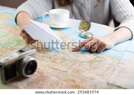 Globetrotter coffee break for trip dreams. Shallow depth of field. woman sitting at table with a map with a paper airplane, compass and camera and visualises his desire to travel - stock photo