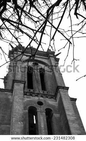 Gloomy ancient church through the bare tree twigs. (Senlis, France). Selective focus on the twigs. Aged photo. Black and white. - stock photo