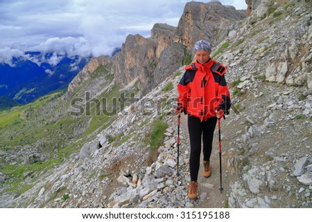Gloomy atmosphere on the mountain with woman hiker on rocky trail and distant clouds,  Dolomite Alps, Italy - stock photo