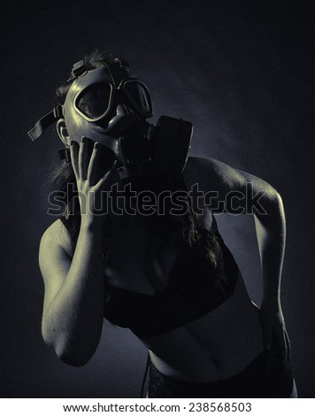 Gloomy atmosphere, sexy woman wearing a gas mask and lingerie - split toning, black and white image, intentional film grain added