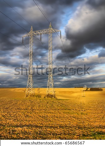Gloomy clouds above the transmission tower situated in the field - stock photo