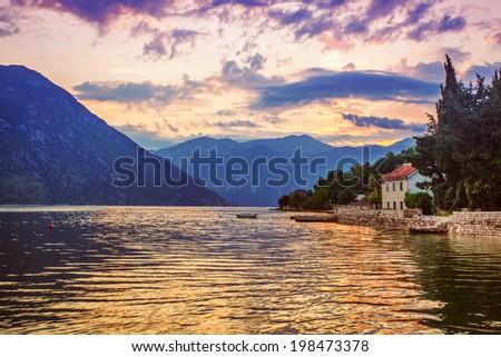 Gloomy sea sunset on mountains background - stock photo