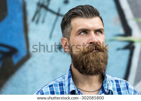 Gloomy serious unshaven guy with long beard and hendlebar moustache in checkered white and light blue shirt looking away standing outdoor on graffiti background copyspace, horizontal picture - stock photo