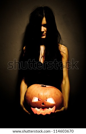 Gloomy woman holding a large glowing orange pumpkin carved for Halloween celebration. Dark background. - stock photo