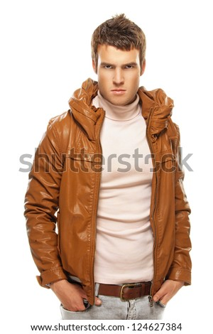 Gloomy young man in brown jacket, it is isolated on black background. - stock photo