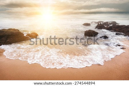 Glorious sunrise scene at the ocean with the sun, clouds and a beautiful little white wave on the sand in the foreground - stock photo