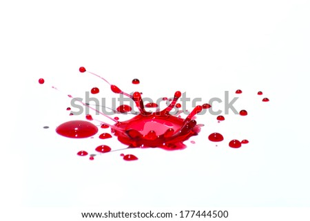 Glossy red liquid droplets (splatters) isolated on white. - stock photo