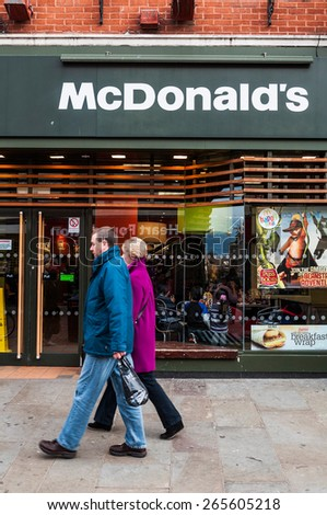 GLOUCESTER, UK - DECEMBER 04: unidentified couple passing by Macdonald's restaurant on December 04, 2011 in Gloucester, UK. McDonald's is the world's largest chain of hamburger fast food restaurants. - stock photo
