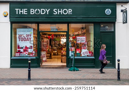 GLOUCESTER, UK - DECEMBER 04: unidentified woman passing by The Body Shop store on December 04, 2011 in Gloucester, UK. Founded in 1976, The Body Shop has over 2600 stores worldwide. - stock photo