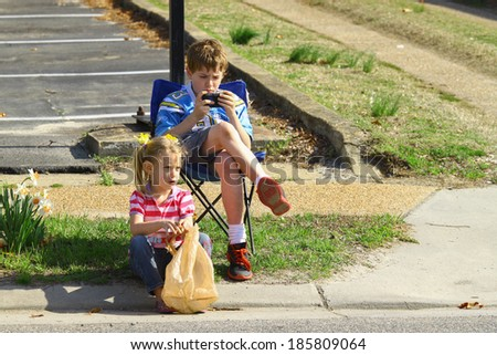 GLOUCESTER, VA - April 5, 2014: A young brother and sister sitting on the curbside awaiting the parade to start, The Daffodil fest and Parade is a regular event held each spring