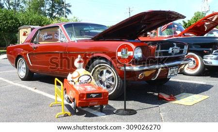 GLOUCESTER, VIRGINIA - AUGUST 22, 2015:A burgundy 1965 OZ mustang and tin man character in the DRIVE-IN FOR DIABETES CAR SHOW Sponsored by Tractor Supply in August in  Gloucester Virginia.