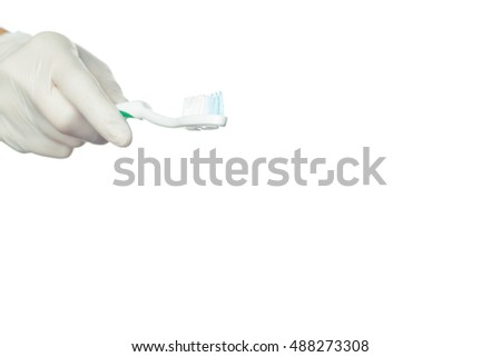 Gloved doctor's hand holding a toothbrush