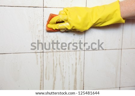gloved hand cleaning dirty old tiles with sponge in a bathroom - stock photo