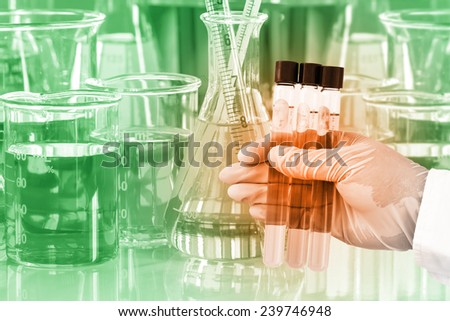 Gloved hand holding the test tubes with glassware in laboratory