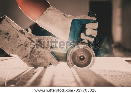 Gloved hand of a construction worker Cutting Ceramic Tile in factory - stock photo