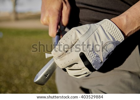 Gloved hand of a golfer holding a four iron golf club and a wooden tee - stock photo