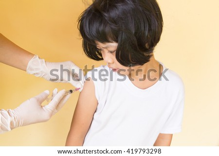 Gloved hand of nurse making an injection to little girl on yellow background - stock photo
