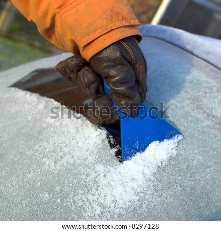 Gloved hand uses scraper to clear ice from car window