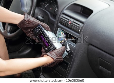 Gloved hands of a thief stealing a car radio from the dashboard of a car with the wiring exposed - stock photo
