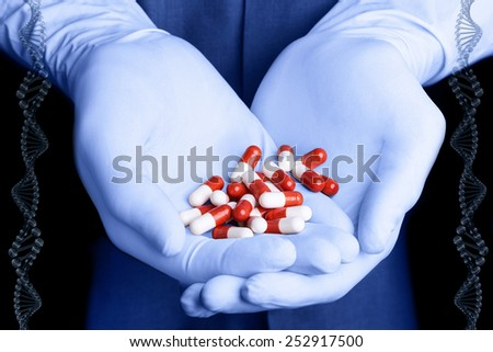 Gloved hands with white-red pills - stock photo