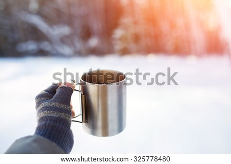 Gloved mitten hand holding a travel mug. WInter forest snowy background. - stock photo