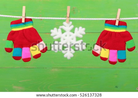 Gloves with snowflake hanging on the clothesline on green wooden background